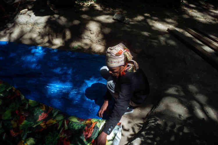 Un migrant prépare son emplacement. Les gardiens du jardin du Bois Dormoy, qui travaillent pour la Mairie de Paris, surveillent l'installation du campement, sans toutefois intervenir.