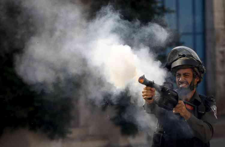 Un policier israélien tire du gaz lacrymogène contre les manifestants palestiniens à Hebron.