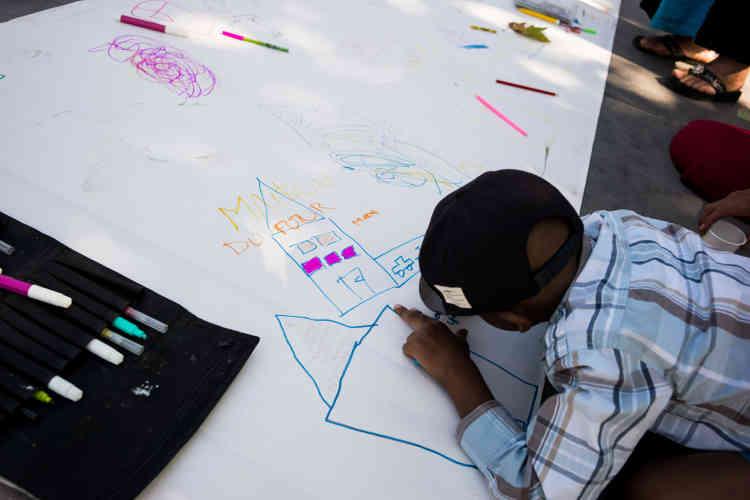 Des enfants dessinent sur une banderole qui devrait être portée au ministère du logement, mercredi 5 août.
