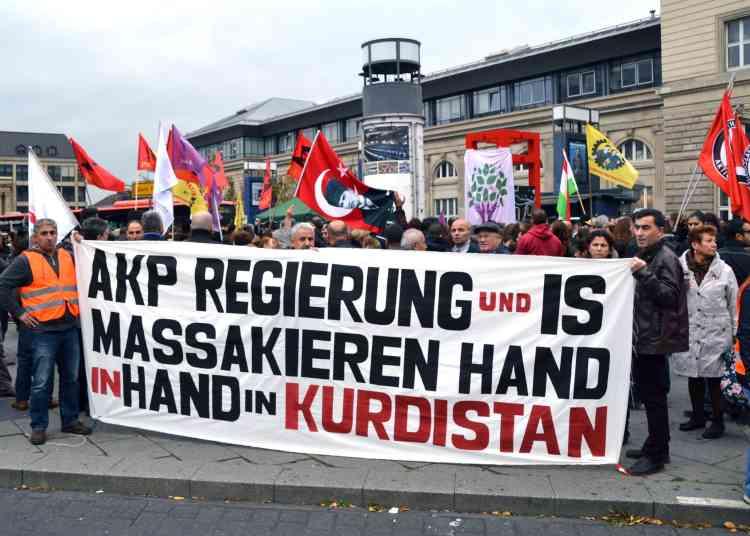 """Une bannière est brandie par des manifestants à Mannheim, en Allemagne. """"Le gouvernement de l'AKP et l'Etat islamique massacrent le Kurdistan main dans la main"""", peut-on y lire."""