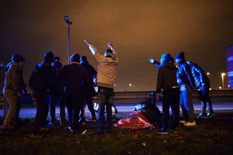 Un groupe de migrants signale à l'ambulance en approche l'emplacement de la victime.