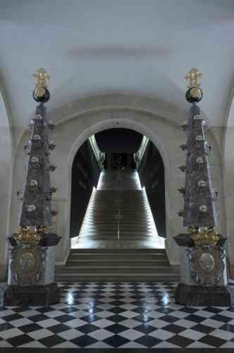 Deux piliers, sur lesquels sont accrochés des crânes, dans la pure tradition baroque, marquent l'entrée de l'exposition dédiée aux funérailles de Louis XIV.
