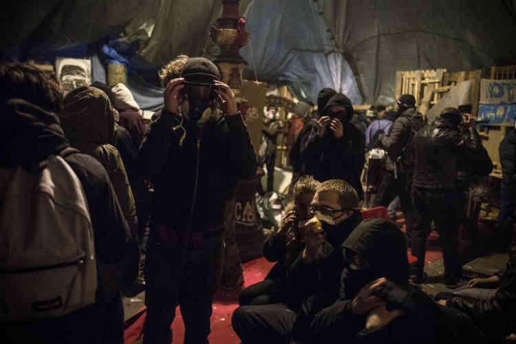 """Des manifestants sous le """"château"""", un chapiteau de fortune, envahi par les gaz lacrymogènes lancés par les forces de l'ordre."""