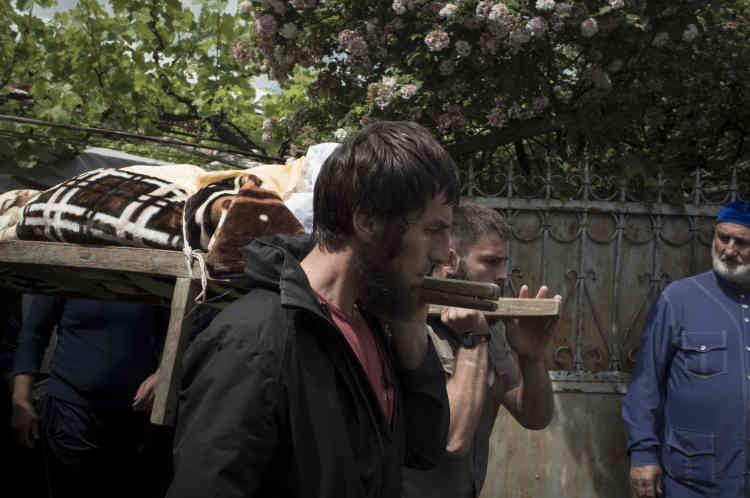 Cérémonie de funérailles : les hommes du village portent le défunt à travers le village jusqu'au cimetière.
