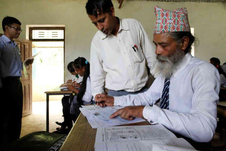 Un enseignant l'aide à remplir le formulaire d'inscription pour la prochaine session d'examen de fin d'études.