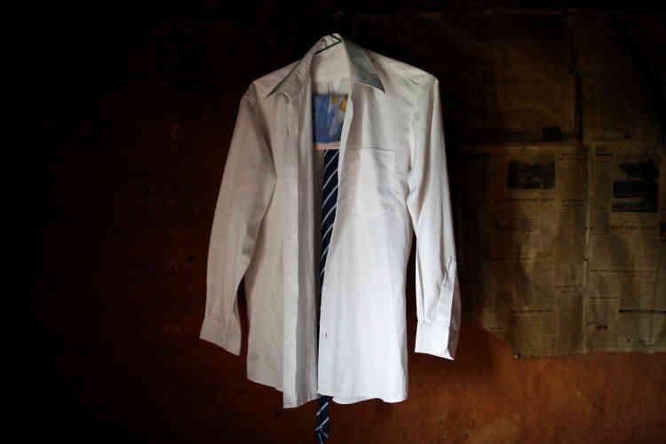 L'uniforme scolaire de Durga Kami accroché au mur de sa maison où il vit seul depuis que sa femme est morte il y a quinze ans.