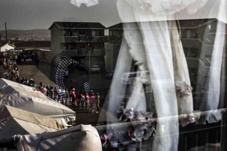 Une femme et un enfant sont aperçus dans le reflet d'une vitre surplombant une file de votants à KwaMashu au nord de Durban.