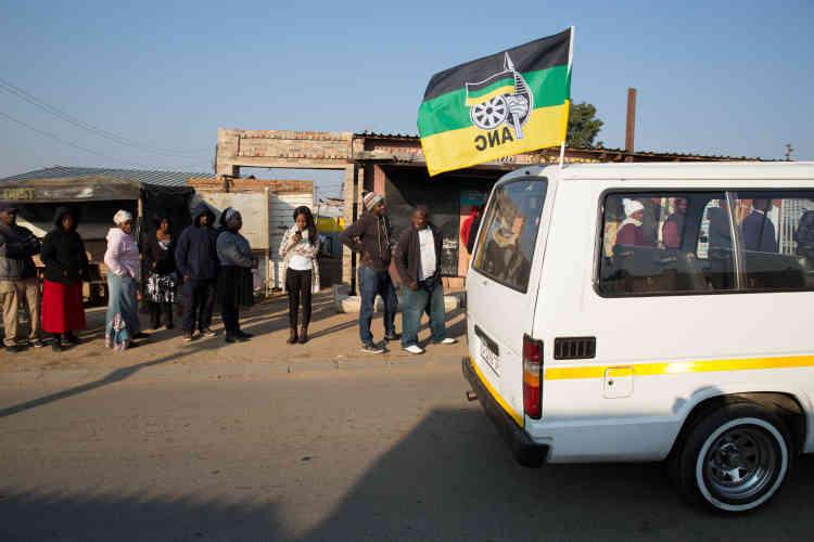 Un taxi avec le drapeaudu Congrès national africain (ANC)circule devant des votants dans le townshipdeDiepsloot, au nord deJohannesbourg.