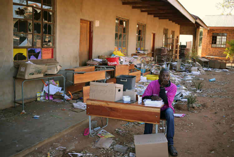 A Vuwani, un membre de la commission électorale indépendante patiente à l'extérieur d'une école endommagée par les émeutes de mai. L'école sert de bureau de vote pour les élections municipales.