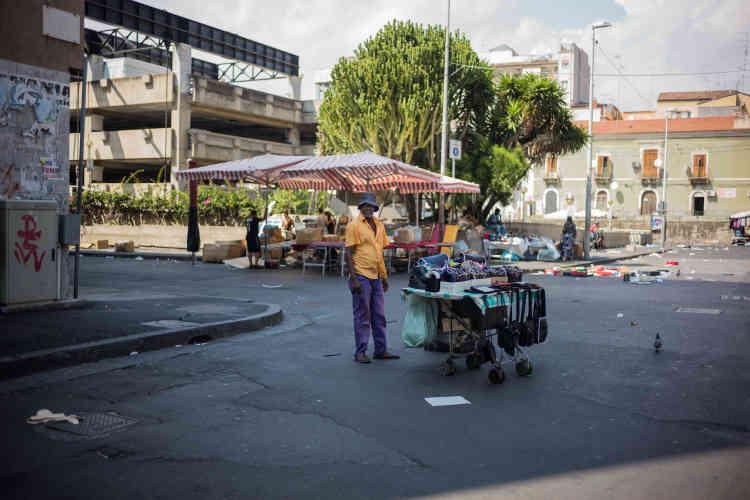 Un vendeur ambulant sur une place de la ville.Dans les squares autour de la gare errent les nouveaux venus. Aux migrants juste débarqués d'Afrique qui ont échappé à l'enregistrement et au transfert vers le nord de l'Italie s'ajoutent ceux qui sont sortis de de la commune de Mineo, déboutés du droit d'asile. Mais il ont décidé de rester.