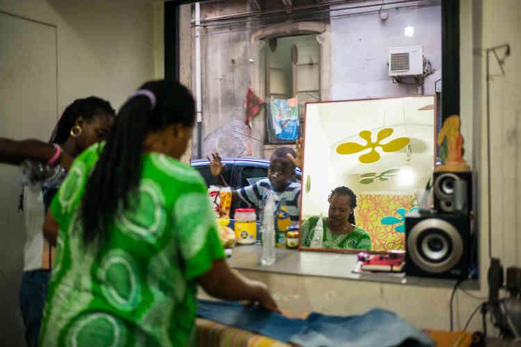 Fatou Diop, une Sénégalaise établie à Catanedepuis longtemps, repasse du linge dans la laverie où elle travaille.