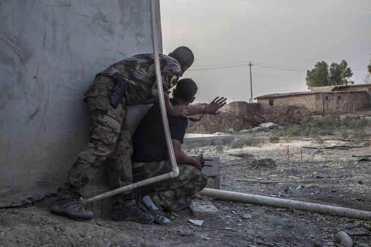 Devant la ville de Bazwaya, le major Salam (pistolet à la ceinture) commandant des divisions de la Division d'or, observe la ligne de front, le 26 octobre.