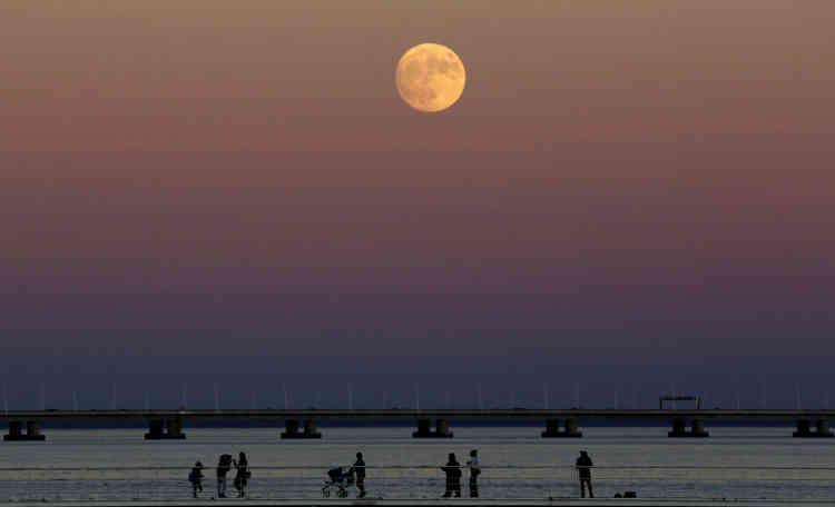La Lune à son lever au-dessus du Tage à Lisbonne, au Portugal.