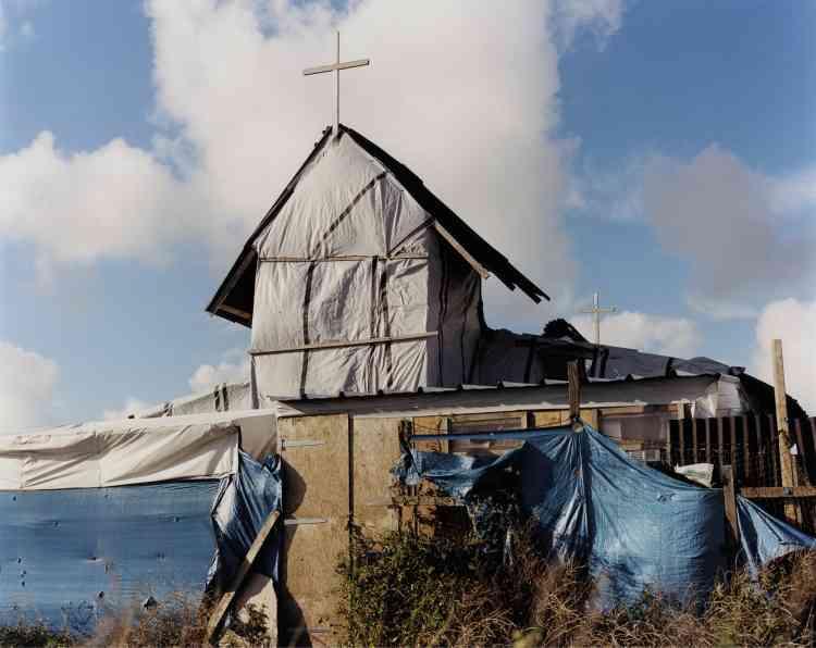 En quelques jours fin octobre, les bulldozers ont emporté les cabanes et tentes construites au fil des mois par les migrants de la « jungle ». Tandis que le campement se vidait de ses milliers d'hommes, la photographe britannique Harley Weir a sillonné ce monde sur le point de disparaître. Saisissant sa misère, mais aussi son ingéniosité et sa poésie. Ici, se dresse une église érythréenne de fortune.