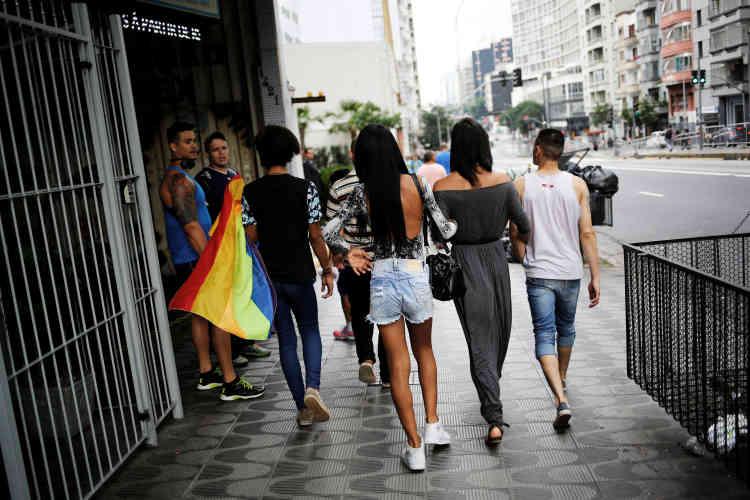 Des hommes regardent passer Gaby, 18 ans, Natalia, 20 ans, Fernanda, 20 ans, et Aleksander, 23 ans, dans une rue de Sao Paulo.
