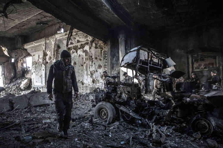 Les forces spéciales dans un palais de Saddam Hussein devant un véhicule détruit de de l'EI.
