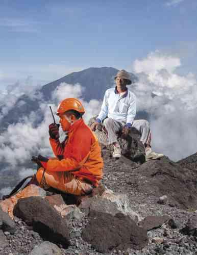 En s'intéressant aux mesures prises par l'Indonésie pour anticiper les catastrophes naturelles, Miguel Hahn et Jan-Christoph Hartung livrent des images à la fois drôles et inquiétantes. Elles racontent aussi la naissance d'un tourisme volcanique. A 20 mètres du cratère du Merapi, à Java, un volcanologue (ici, avec son porteur) communique avec le technicien en train d'installer un GPS destiné à mesurer l'activité sismique du volcan.