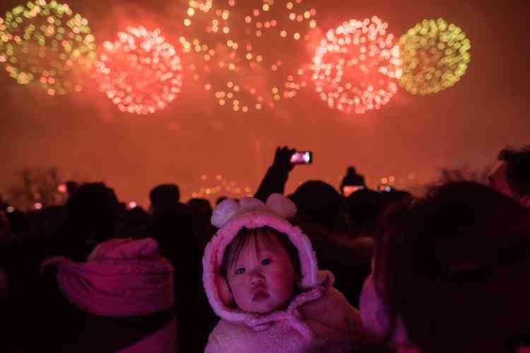 Soldats, fonctionnaires, familles et enfants regardent le feu d'artifice près de la rivière Taedong à Pyongyang.