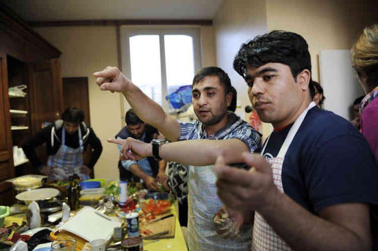 Ahmad dirige les opérations avec Mohammed Agha. A l'initiative du Collectif de Serquigny, commune de l'Eure qui a accueilli près de trente réfugiés en novembre 2016, dejeunes Afghans préparent des plats traditionnels avec les habitants. Dans la salle des fêtes de Fontaine-l'Abbé, une commune voisine, le 25 février.
