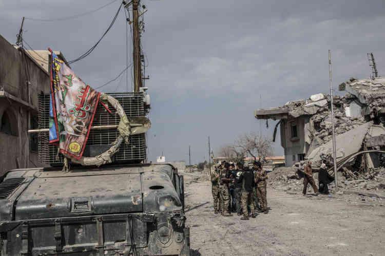 Des combattants de la police fédérale, drapeau religieux chiite exhibé sur le Humvee, dans les quartiers repris à l'EI, le 8 mars.