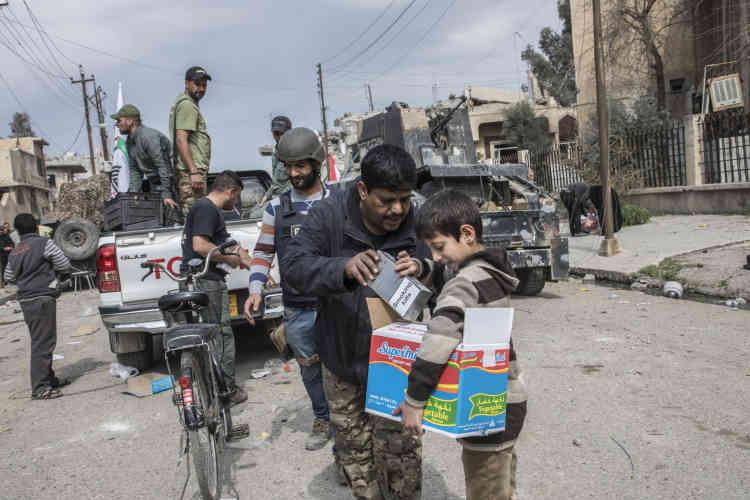 Des membres de la Mobilisation populaire chiite distribuent de la nourriture et des cigarettes dans les quartiers de Mossoul-Ouest repris par les divisions de réaction d'urgence, le 8 mars.
