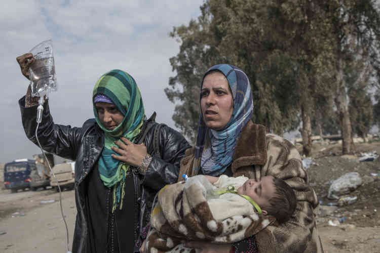 Deux femmes et un bébé fuient les combats en direction de l'aéroport, le 8 mars.