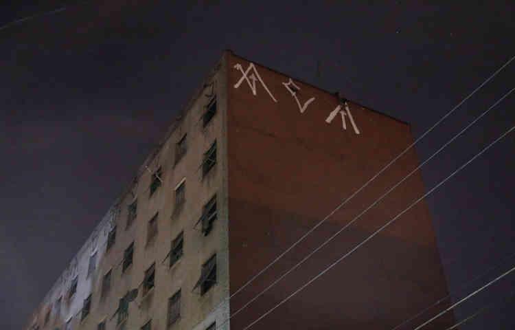 Un «pixador», dont le nom provient du style de graffiti, intervient au sommet d'un immeuble.