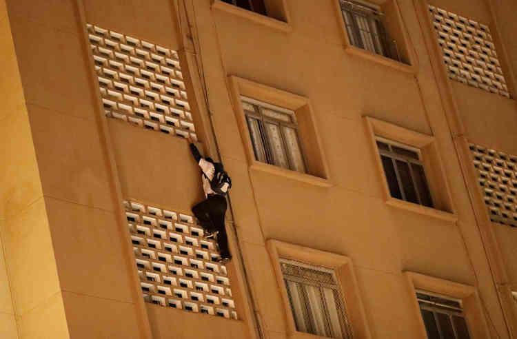Un jeune homme escalade un immeuble de neuf étages pour y placer son tag.