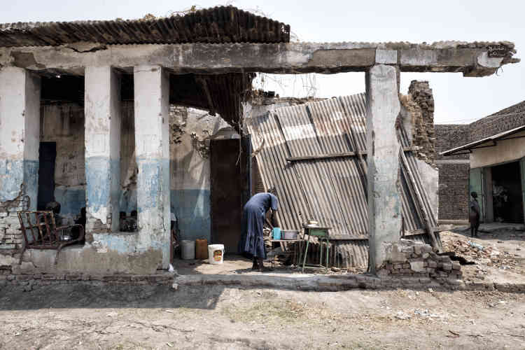 Une femme lave sa vaisselle dans les décombres d'une maison de Malakal.