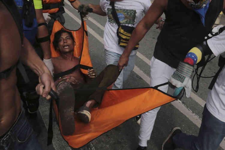 Un homme est évacué après avoir été brûlé lorsque des manifestants ont incendié une moto de la Garde nationale bolivarienne, mercredi 3 mai, à Caracas.