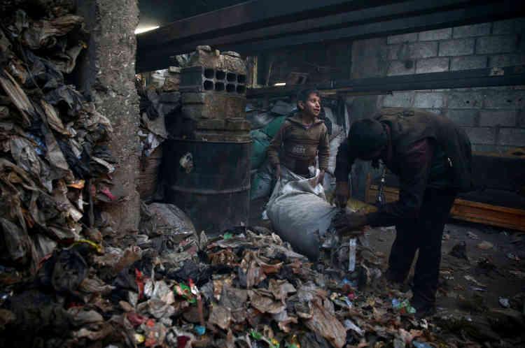 Un garçon et un adulte trient les plastiques dans un atelier.La raffinerie fonctionne depuis trois ans et demi, depuis que les forces gouvernementales ont commencé le siège de la Ghouta, un secteur de la banlieue de Damas dans lequel se situe la ville de Douma.