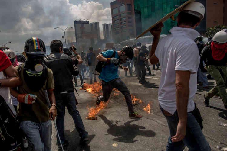 Les altercations entre forces armées et manifestants sont d'une grande violence. Ici un manifestants tente d'éviter un cocktail Molotov, le 10 mai.