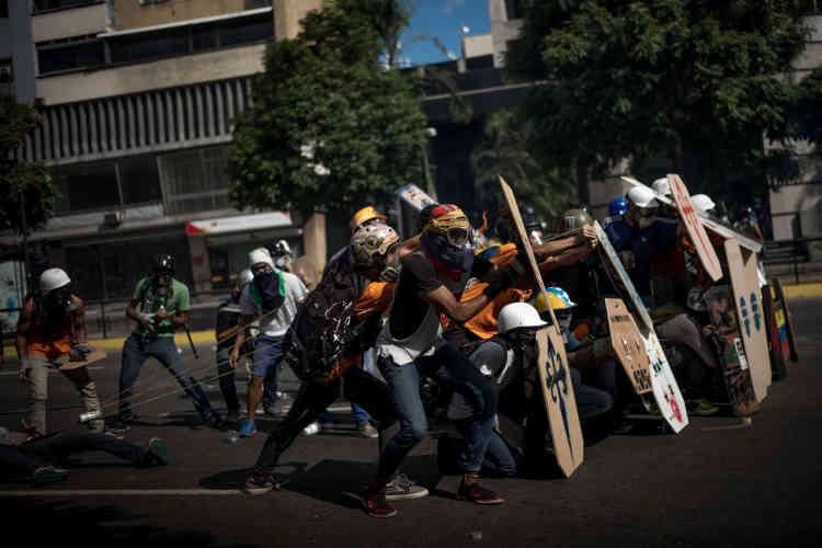 Les manifestants se protègent alors qu'une catapulte est envoyée sur les forces de l'ordre, le 20 mai.