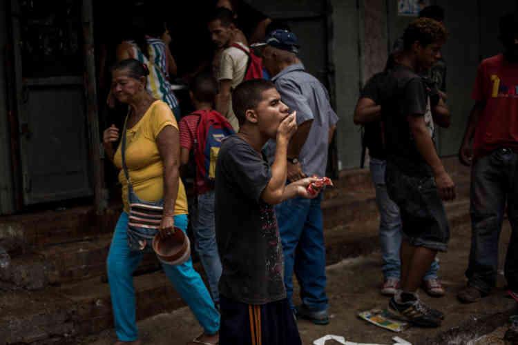 A la Vega, un homme se nourrit après avoir fait les poubelles.