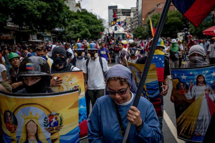 Une religieuse est escortée durant une manifestation.