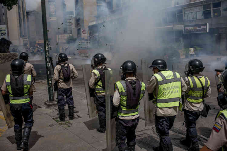 Des forces de l'ordre progressent vers les manifestants.