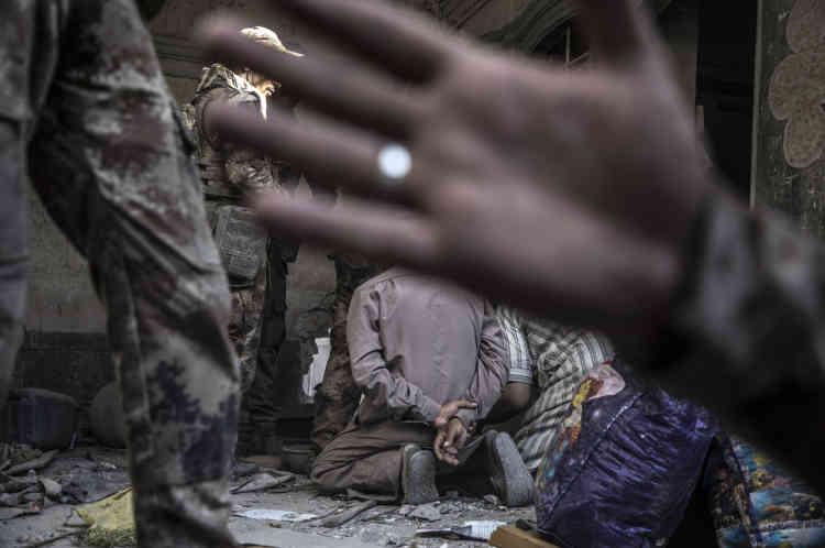 Trois hommes sortent ensuite, que des membres des forces spéciales soupçonnent d'être également des éléments de l'organisation Etat islamique.