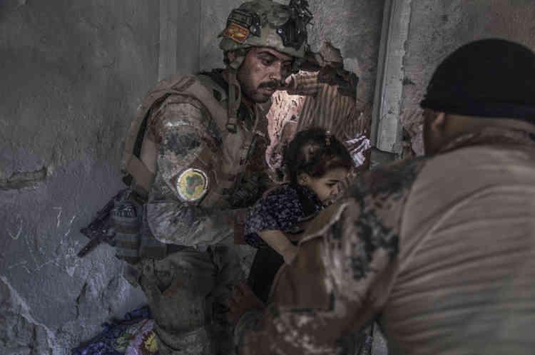 Des soldats des forces spéciales évacuent des enfants par une ouverture faite à la masse quelques minutes plus tôt.