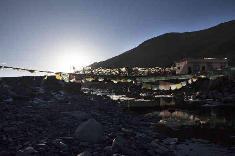 Des drapeaux de prière tibétains flottent sur un pont qui traverse le Liqi. En 2013 et 2016, la mine Rongda a déversé des matières toxiques dans la rivière, provoquant la mort de nombreux poissons.