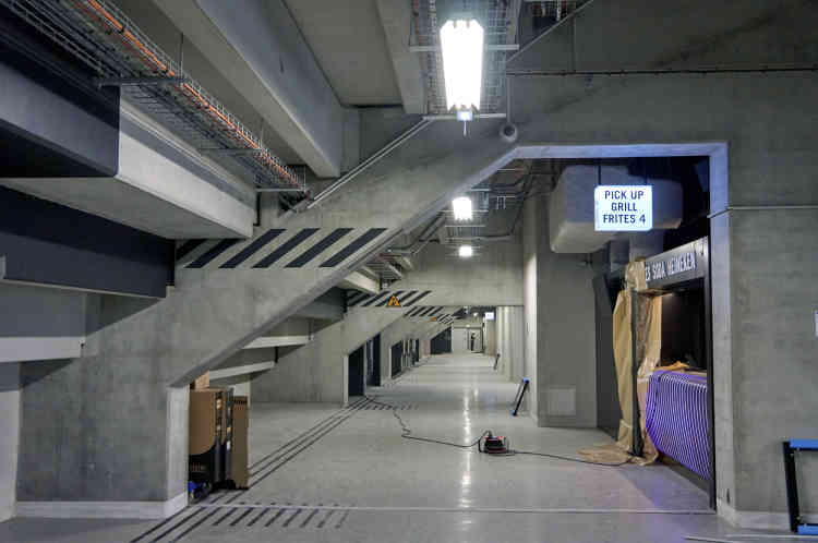 L'une des galeries de circulation qui permet d'accéder à la salle. Il a été décidé de conserver la teinte grise du béton, qui a été traité et lissé pour atténuer son aspect brut. A cette dominante, répond l'utilisation du noir dans l'environnement des différentes boutiques, espaces de restauration et buvettes.
