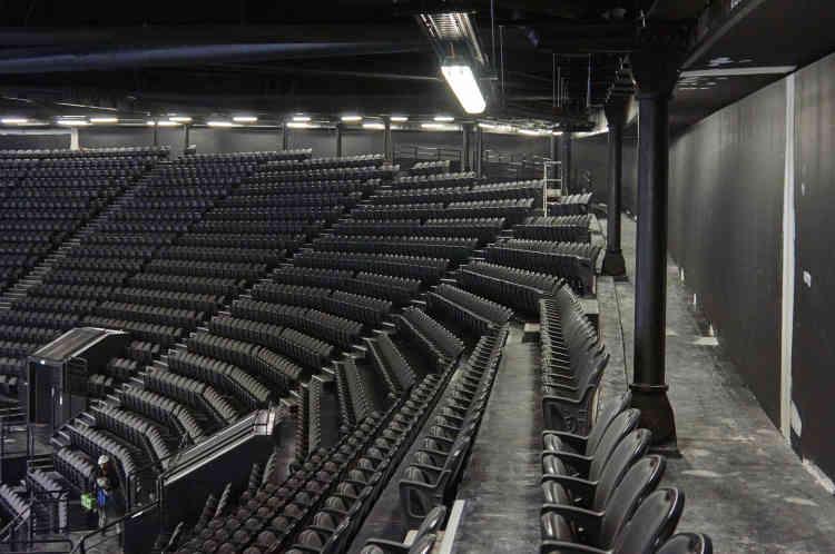 Vue du troisième niveau de gradins de l'U Arena. La charpente métallique du toit est à 40 mètres du sol. Elle reçoit les quarante-quatre appareils qui permettront des projections dans l'ensemble de la salle, au sol et vers un espace mural pouvant aller jusqu'à une surface de2500 mètres carrés.
