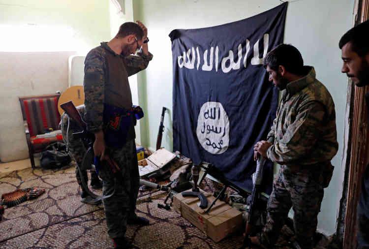 Des soldats des Forces démocratiques syriennes examinent des munitions et des armes prises aux combattants de l'EI, dans un immeuble situé sur la ligne de front, le7octobre.