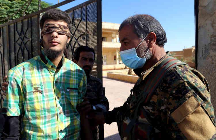 Un soldat des Forces démocratiques syriennes (à droite) escorte un civil suspecté d'être membre de l'EI, le 12 octobre.