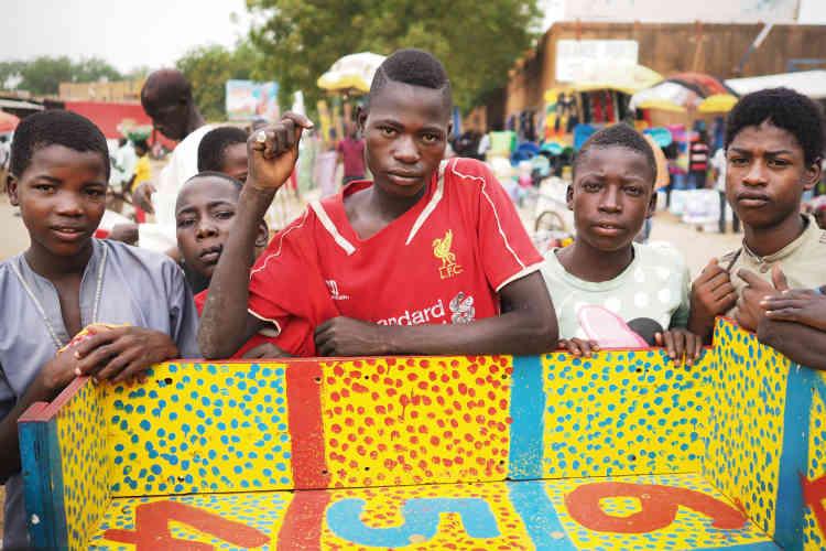 Les enfants jouent au « sisilido», un jeu de dés, surle grand marché de Niamey.