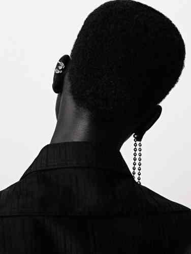 Boucle d'oreille serti sur vide en or blanc pavé et serti de diamants, Repossi. Boucle d'oreille Ball Chain en or, Ambush. Robe chemise en coton, Céline.