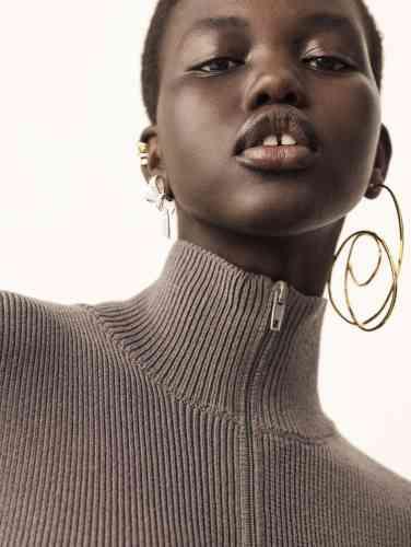 Boucle d'oreille asymétrique Coco Crush en or jaune et or blanc sertis de diamants. Boucle d'oreille Ruban en or blanc serti de diamants, les deux Chanel Joaillerie. Bijou d'oreille round elastic argenté et pull zippé enlaine, Balenciaga.