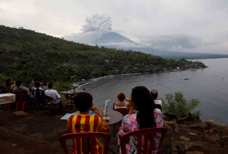 Des gens regardent le volcan Agung d'un café près d'Amed, dans la préfecture de Karangasem. « Ce que nous observons en ce moment, ce sont de petites explosions, qui rejettent des gaz chauds et des fragments de roche fondue ou des cendres », explique David Pyle, professeur des sciences de la Terre à l'université d'Oxford. « La probabilité d'une grande éruption est élevée, mais cela pourrait prendre des jours ou des semaines avant que cela ne se produise », a-t-il ajouté.