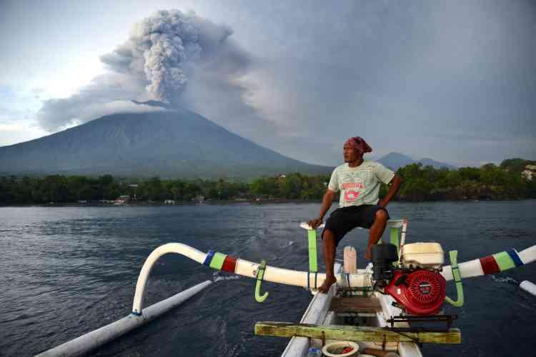 Un pêcheur conduit un bateau traditionnel. Le volcan a donné les premiers signes de réveil en septembre, nécessitant l'évacuation de144000habitants.L'activité avait semblé se calmer à la fin d'octobre, et l'alerte avait été rabaissée, ce qui avait convaincu des milliers de personnes de rentrer. Jusqu'à ce qu'il se remette à gronder voilà quelques jours.