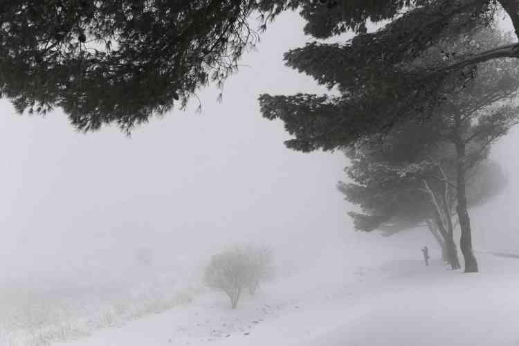 Une femme photographie la neige.