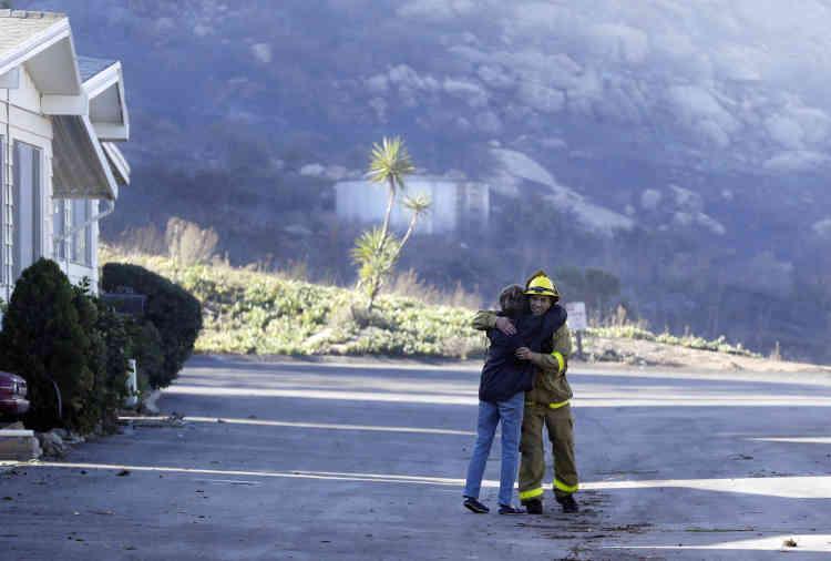 Une habitante de Fallbrook remercie un pompier près de sa maison épargnée par l'incendie.